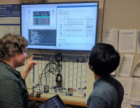 Thom Cuddihy (left), a QCIF/RCC bioinformatician and software developer, demonstrates the cloud compute environment to Microbial Genomics Lab student Budi Permana.